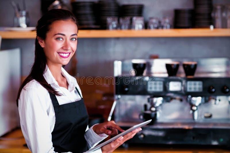 Porträt der lächelnden Kellnerin, die digitale Tablette verwendet stockbild