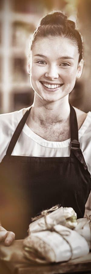 Porträt der lächelnden Kellnerin einen Behälter mit Sandwichen halten stockbild