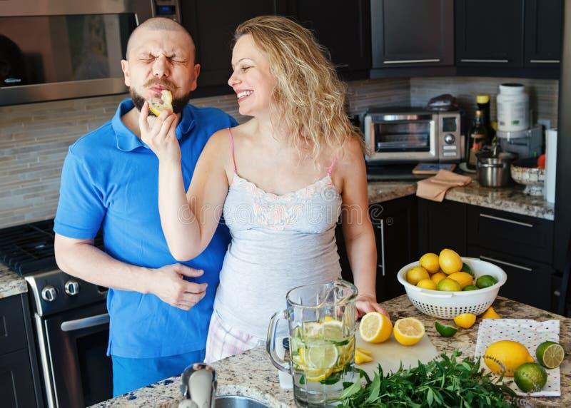 Porträt der lächelnden lachenden schwangeren Frau der weißen kaukasischen Leute der Paare zwei mit dem Ehemann, der Lebensmittel, lizenzfreie stockfotografie