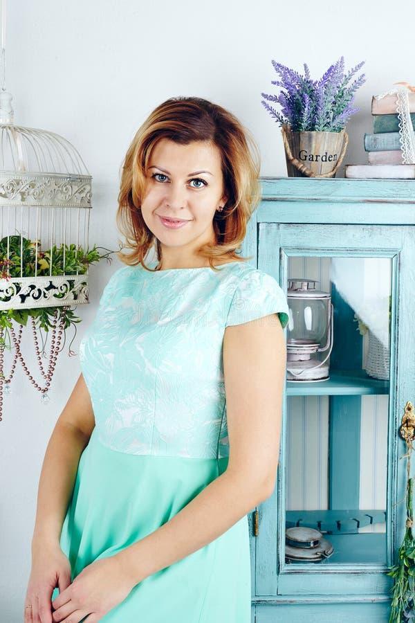 Porträt der lächelnden mittleren erwachsenen Frau, die blaues Kleid trägt stockbilder