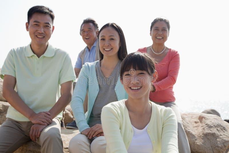 Porträt der lächelnden multigenerational Familie, die draußen auf den Felsen, China sitzt lizenzfreies stockbild