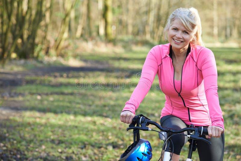 Porträt der lächelnden reifen Frau auf Zyklus-Fahrt in der Landschaft stockfotografie