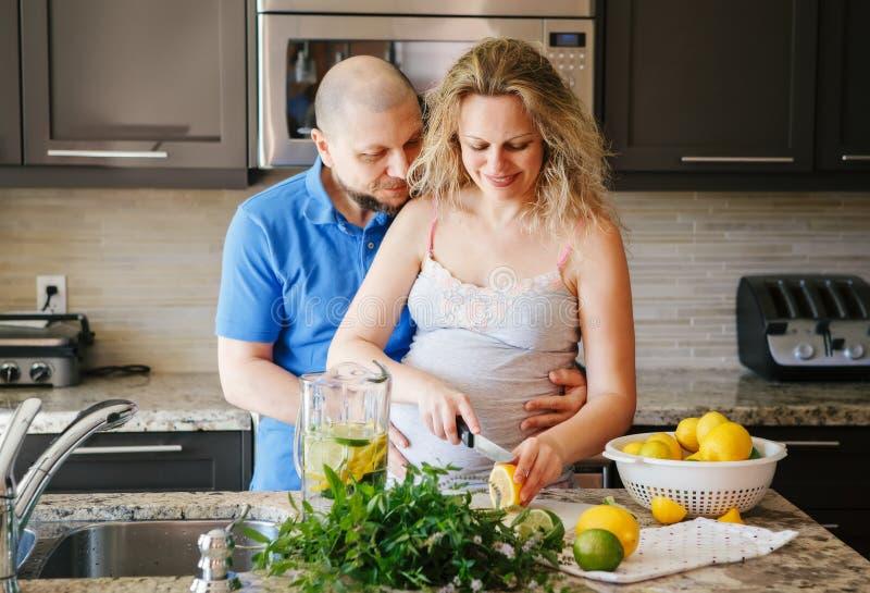 Porträt der lächelnden schwangeren Frau der weißen kaukasischen Leute der Paare zwei mit dem Ehemann, der Lebensmittel kocht stockfotos