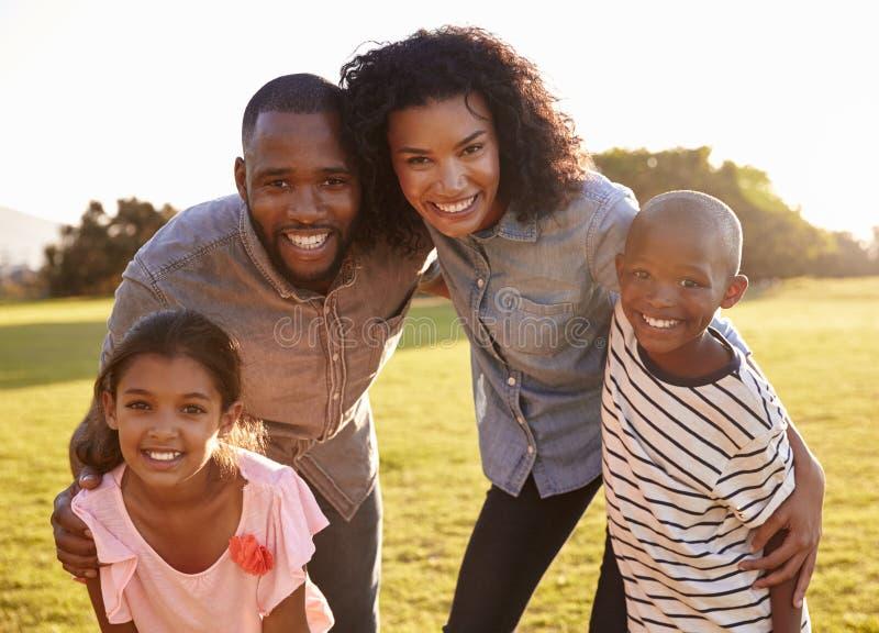 Porträt der lächelnden schwarzen Familie, die draußen zur Kamera schaut stockbild