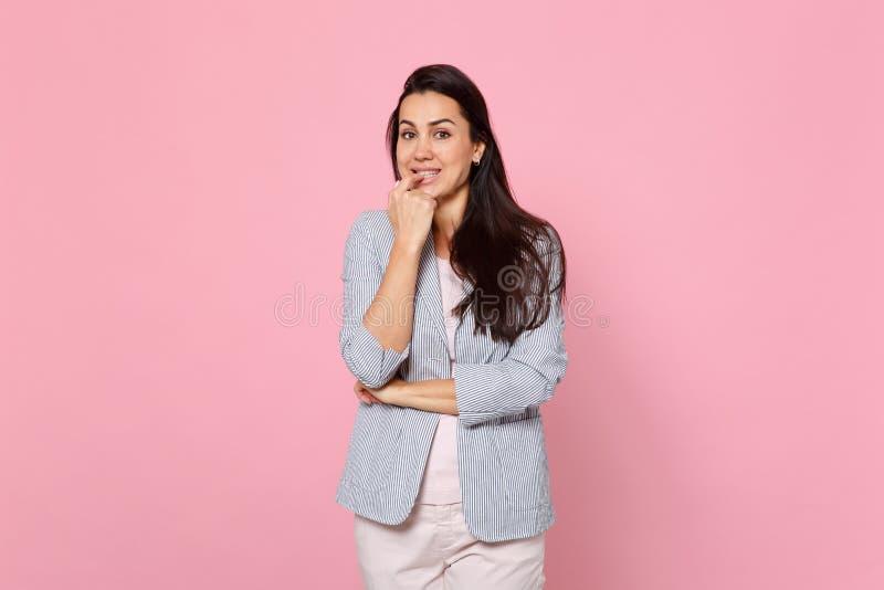 Porträt der lächelnden ungeduldig jungen Frau in gestreifter Jackenstellung, Zerfressennägel lokalisiert auf rosa Pastellwand stockbilder
