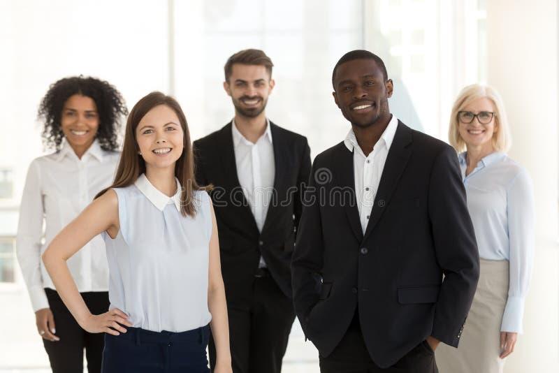 Porträt der lächelnden verschiedenen Arbeitsteamstellung, die im Büro aufwirft stockfotografie