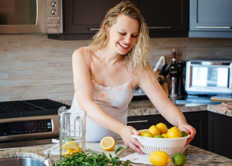 Porträt der lächelnden weißen kaukasischen blonden schwangeren Frau mit der Zitrusfruchtkalkzitrone, die den Saft steht in der Kü lizenzfreies stockbild