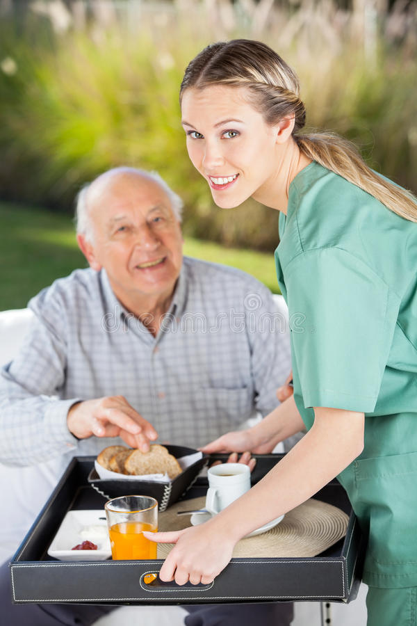 Porträt der lächelnden weiblichen Krankenschwester Serving Breakfast stockfotos