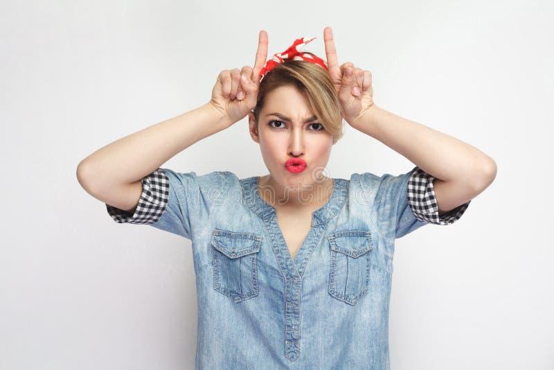 Porträt der lustigen schönen jungen Frau im zufälligen blauen Denimhemd mit Make-up und roter Stirnbandstellung mit den Hornhände lizenzfreie stockfotografie