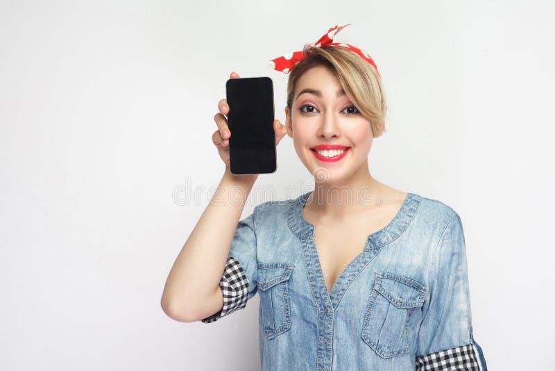 Portr?t der lustigen sch?nen jungen Frau im zuf?lligen blauen Denimhemd mit Make-up und roter Stirnbandstellung, Smartphone nahe  lizenzfreie stockfotos