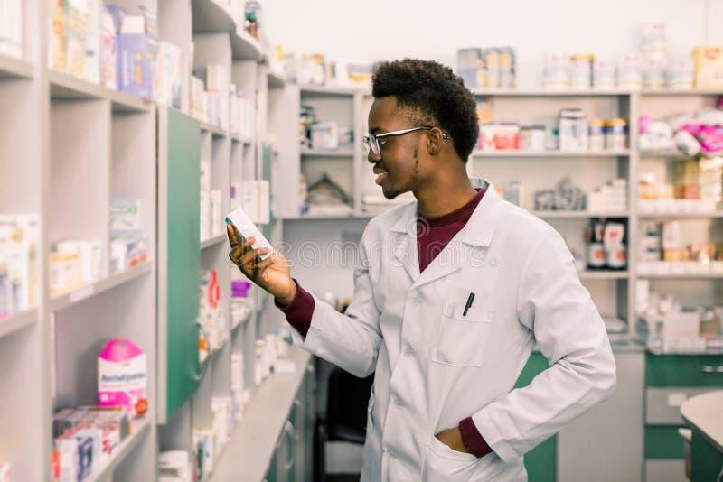Porträt der männlichen Apothekerstellung des Afroamerikaners im Innenraum der Apotheke und die Medizin in der Hand betrachten stockfoto