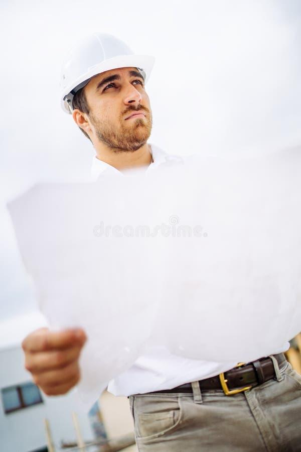 Porträt der männlichen Arbeitskraft auf Baustelle, tragender Schutzhelm und Ablesenpläne lizenzfreie stockfotografie