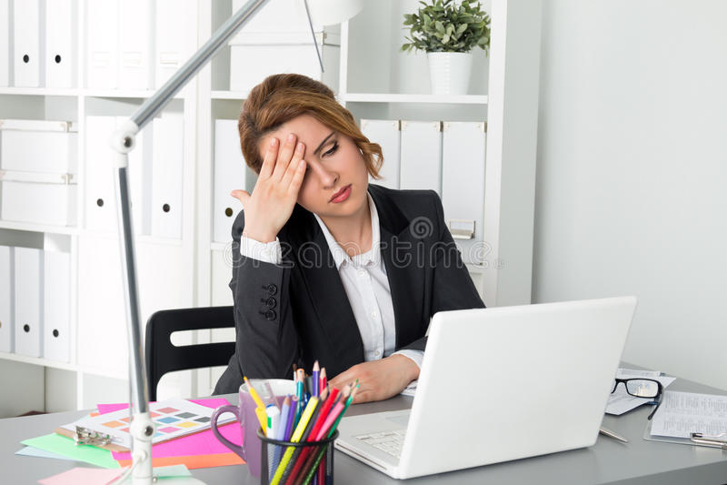 Porträt der müden Geschäftsfrau sitzend in ihrem Büro lizenzfreies stockfoto