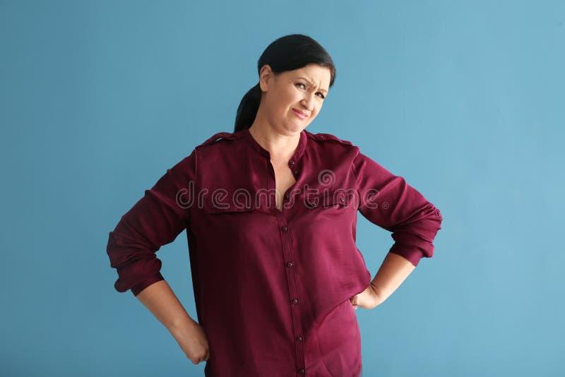 Porträt der missfallenen reifen Frau auf Farbhintergrund stockfoto
