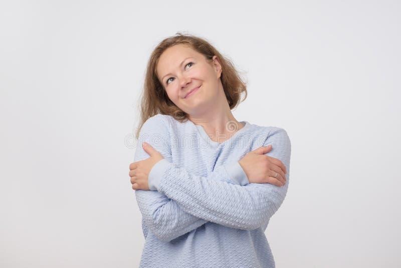 Porträt der Mitte alterte die hübsche Frau in der blauen Strickjacke vortäuschend, wie sie sich umarmt stockfotografie