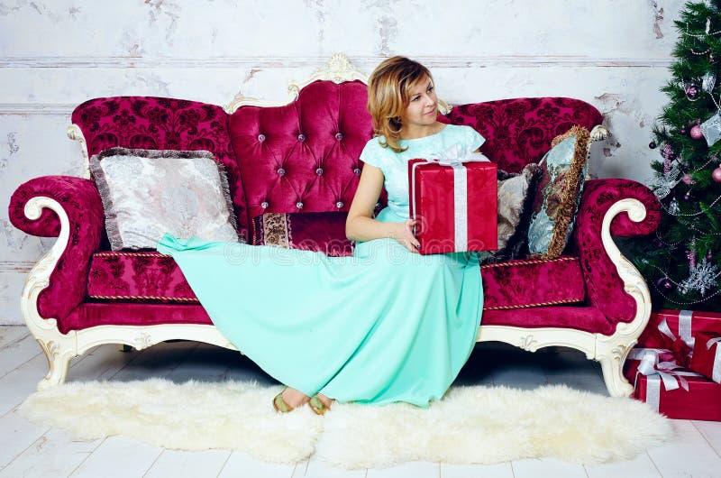 Porträt der mittleren erwachsenen Frau, die auf Sofa mit Weihnachtsgeschenk sitzt stockfotos