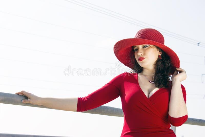 Porträt der Modefrau im roten Kleid und im Hut auf der Brücke stockfotografie