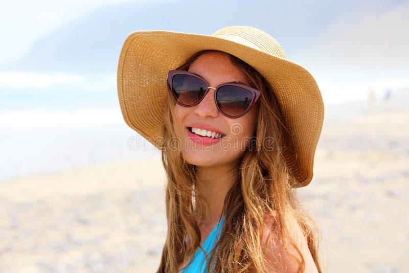 Porträt der Modestrandfrau am sonnigen windigen Tag, der Kamera betrachtet Schließen Sie oben vom schönen Mädchen mit Sonnenbrill stockfoto