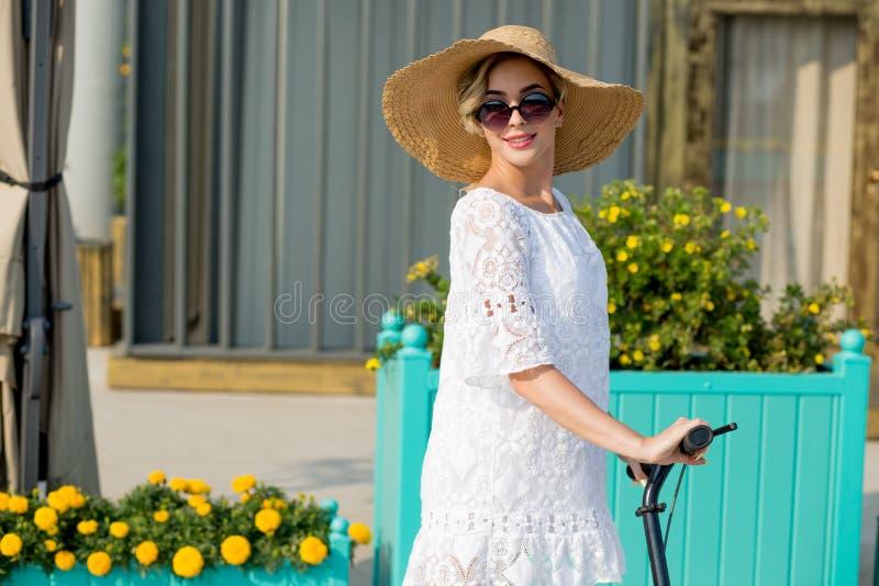 Porträt der modischen Frau, des schönen blonden Mädchens im weißen Kleid, der Sonnenbrille und des Hutreitrollers lizenzfreie stockfotos