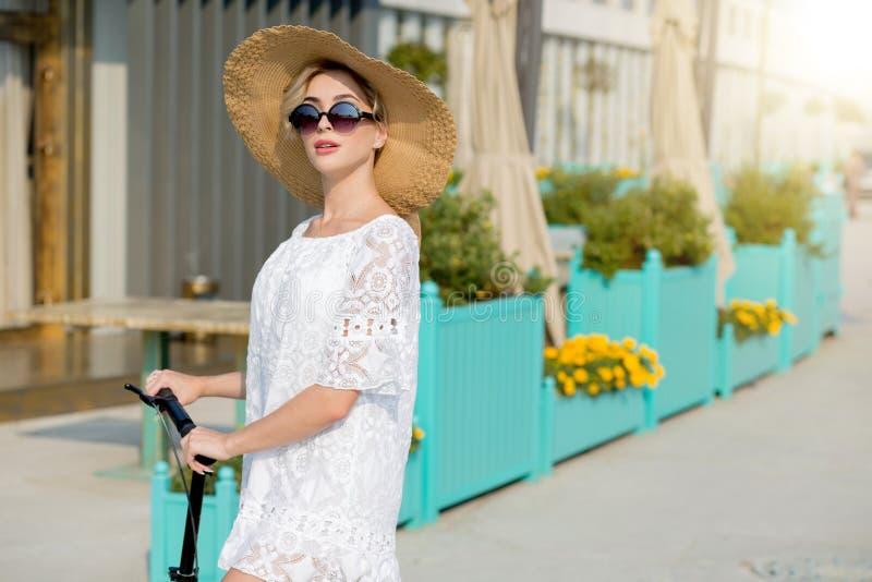 Porträt der modischen Frau, des schönen blonden Mädchens im weißen Kleid, der Sonnenbrille und des Hutreitrollers stockfotos