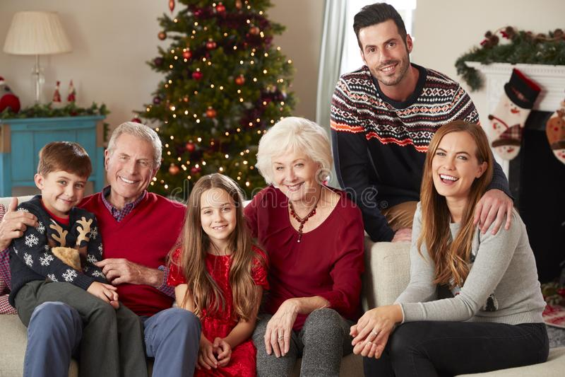 Porträt der multi Generations-Familie, die auf Sofa In Lounge At Home am Weihnachtstag sitzt stockfotografie