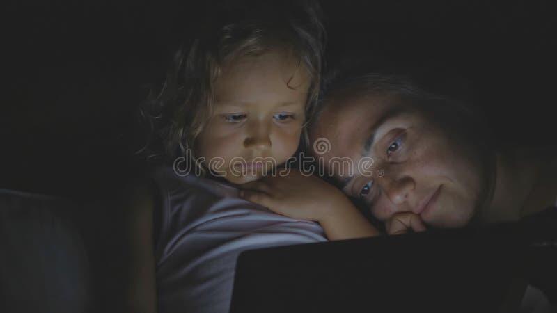 Porträt der Mutter mit der kleinen Tochter, die zu Hause Tablette im Bett bis zum Nacht verwendet stockbild