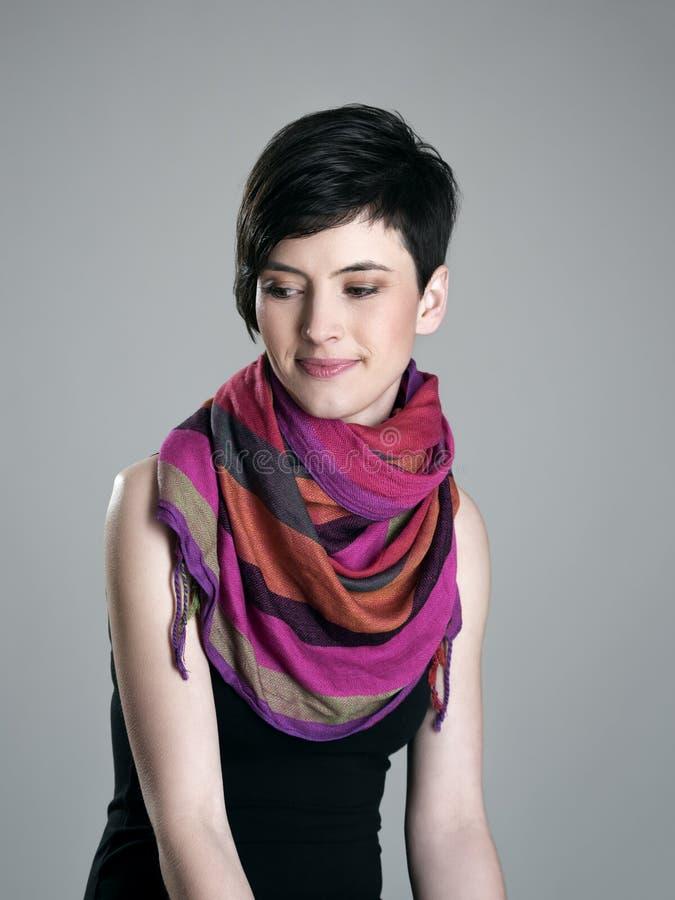 Porträt der nachdenklichen lächelnden Frau des kurzen Haares mit dem bunten Schal, der unten schaut lizenzfreie stockbilder