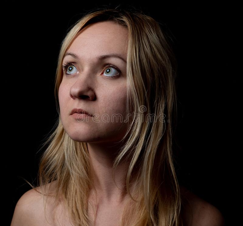 Porträt der natürlichen jungen Frau oben und, die nach links mit schwarzem Hintergrund schaut stockfotografie