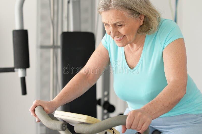 Porträt der netten älteren Frau, die in der Turnhalle trainiert lizenzfreies stockfoto