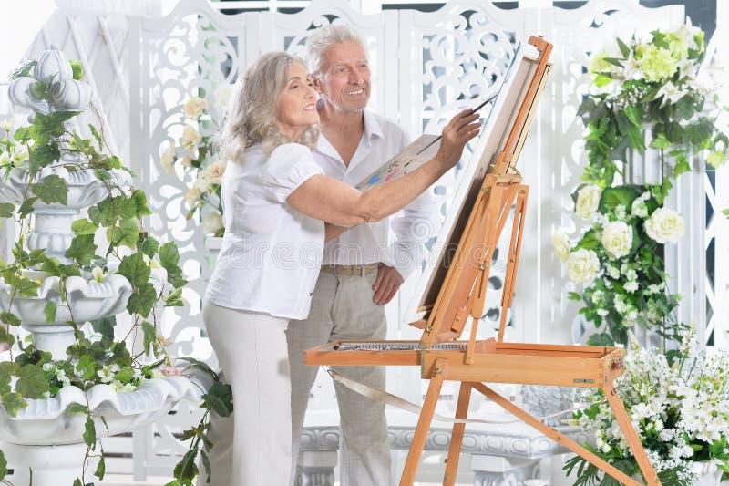 Porträt der netten älteren Paarmalerei zu Hause lizenzfreie stockfotografie