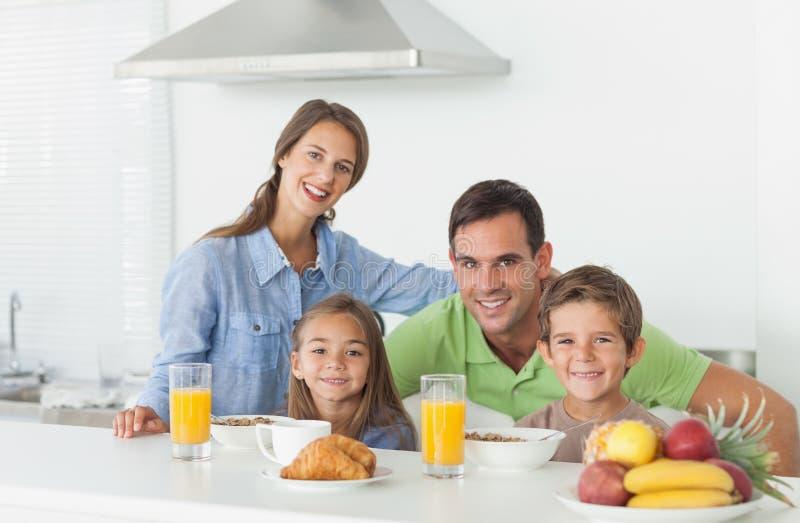Porträt der netten Familie, die frühstückt stockbild