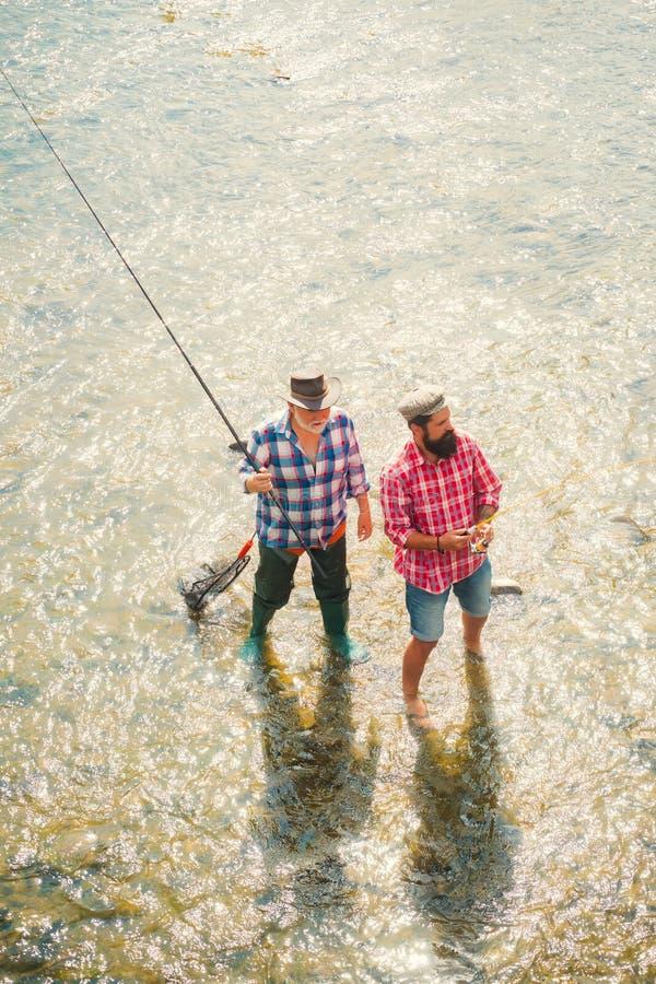Porträt der netten Fischerei mit zwei bärtigen Männern Mannfischer f?ngt einen Fisch Fliegenfischen f?r Forelle angler Vater mit stockfoto