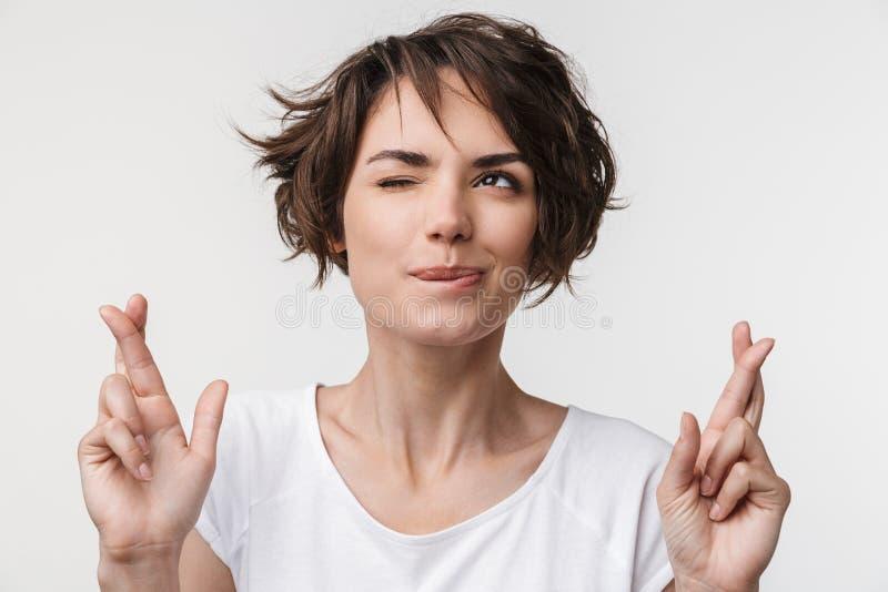Porträt der netten Frau mit dem kurzen braunen Haar im grundlegenden T-Shirt, das Finger gekreuzt hält und Glück wünscht stockfotos