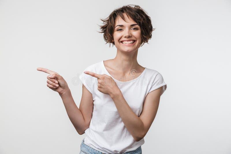 Porträt der netten Frau mit dem kurzen braunen Haar im grundlegenden T-Shirt Finger auf copyspace freuend und zeigend stockfoto