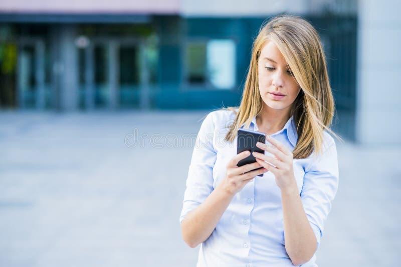 Porträt der netten jungen Frau, die auf Smartphone spricht und draußen lacht stockbild