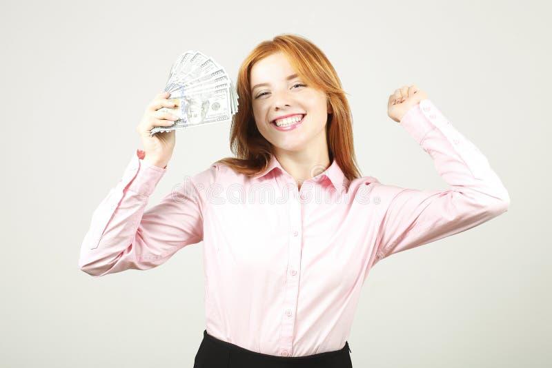 Porträt der netten jungen Frau, die Bündel von hundert Dollarscheinen hält und in gewinnender Haltung, Hände hob feiert oben, Fau stockfotografie