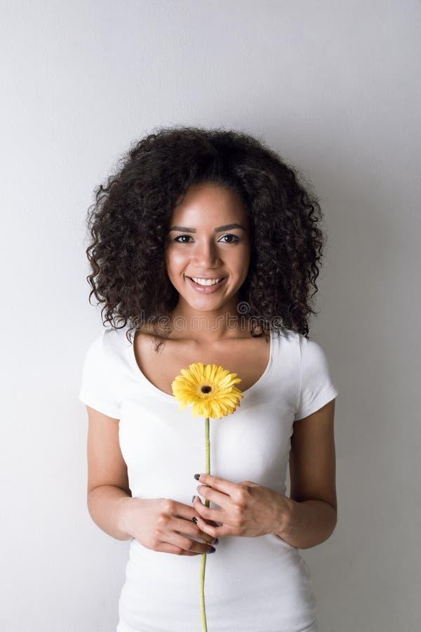 Porträt der netten jungen Frau, die eine gelbe Blume hält stockfoto