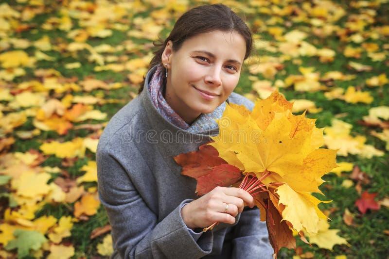 Porträt der netten jungen Frau mit einem bunten Blumenstrauß des gelben Herbstlaubs im Park im Herbst stockbilder