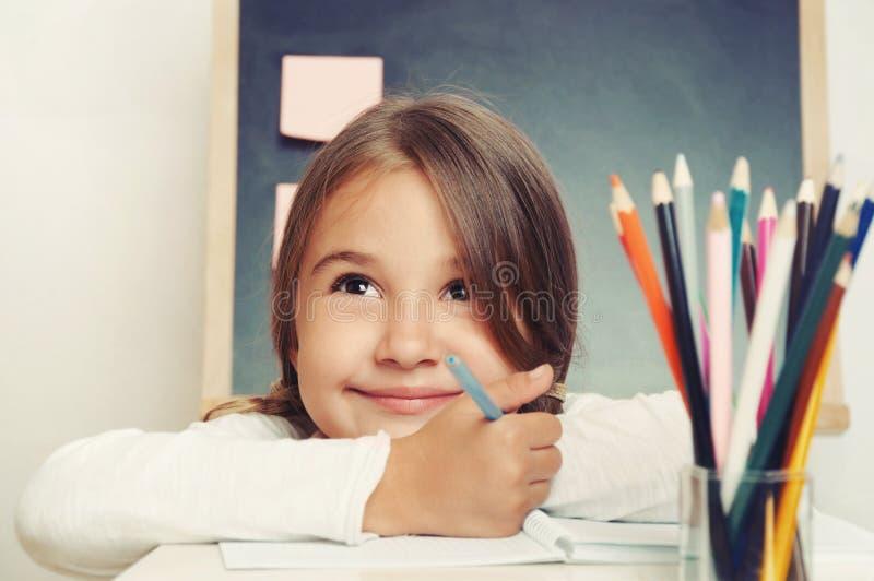 Porträt der netten reizenden Mädchenzeichnung im Schreibheft auf Tafel b lizenzfreie stockbilder