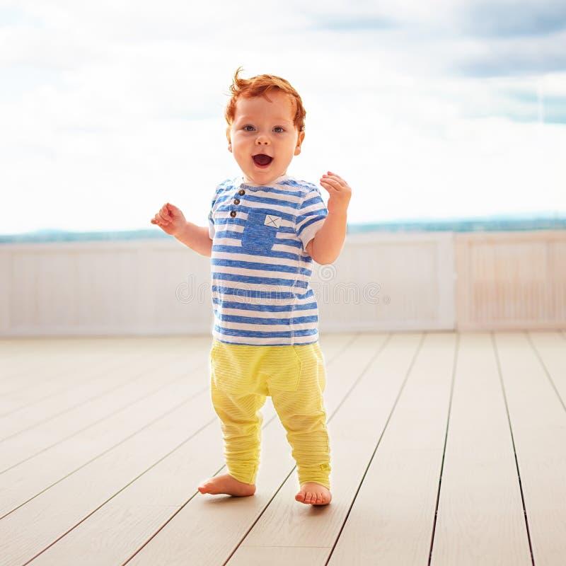 Porträt der netten Rothaarigen, ein jähriges Baby, das auf Decking geht stockfotos