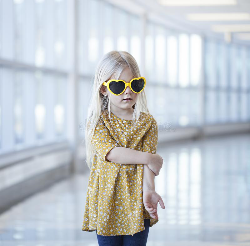 Porträt der netten tragenden Herz-förmigen Sonnenbrille des kleinen Mädchens lizenzfreies stockbild