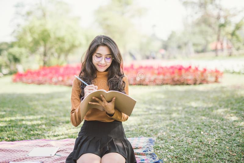 Porträt der Oberschülerin denkend und gelesen einem Buch im Park, Bildungslesebuch und denkendem kreativem Ideenkonzept lizenzfreie stockbilder
