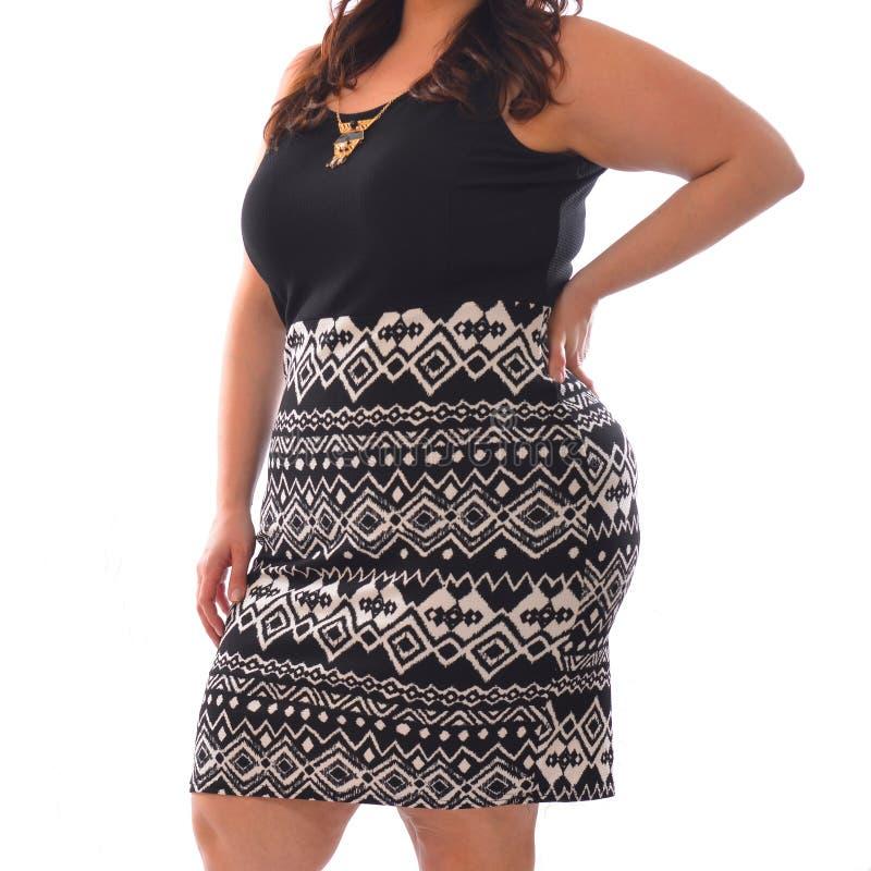 Porträt der Plusgrößenmodellfrau, die schwarze T-Shirt und Rockaufstellung XXL lokalisiert auf Weiß trägt stockfoto