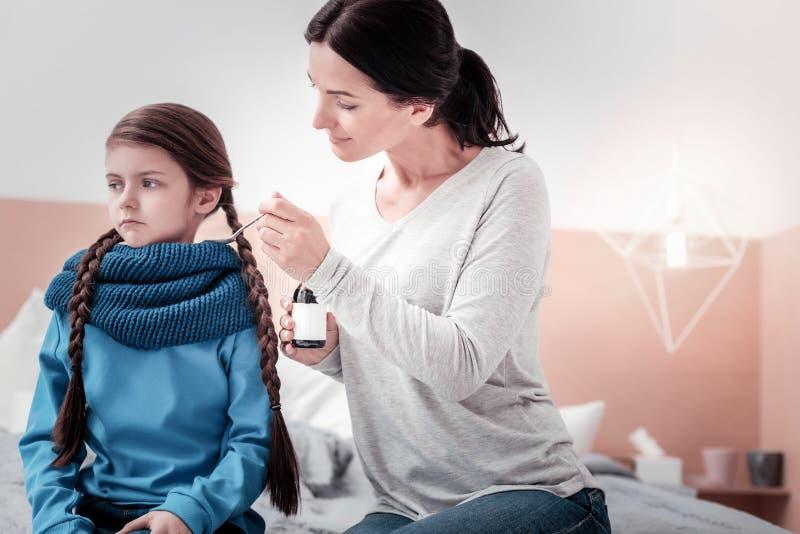 Porträt der positiven Mutter Hustensirup gebend ihrer Tochter lizenzfreies stockbild