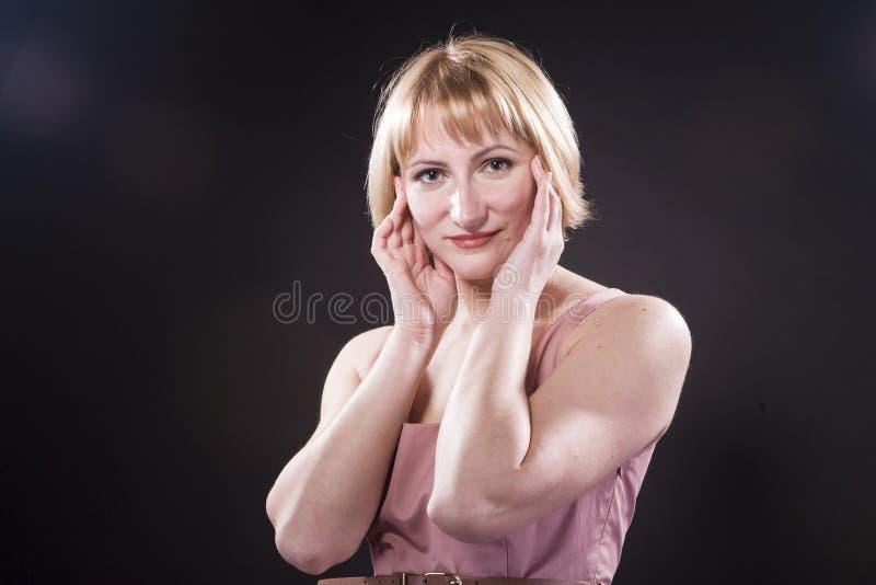 Porträt der positiven optimistischen kaukasischen blonden Frau im rosa Kleid lizenzfreie stockfotografie