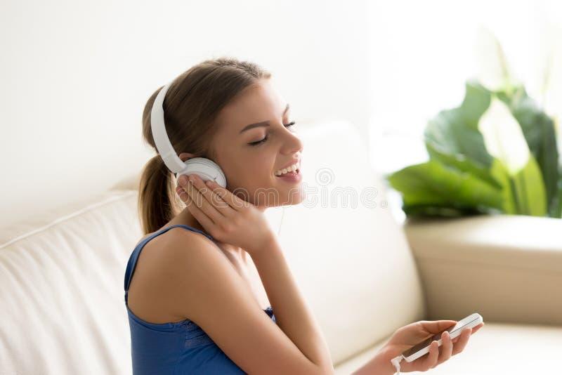 Porträt der recht jungen Frau in den Kopfhörern, die auf Sofa sitzen und lizenzfreie stockfotos