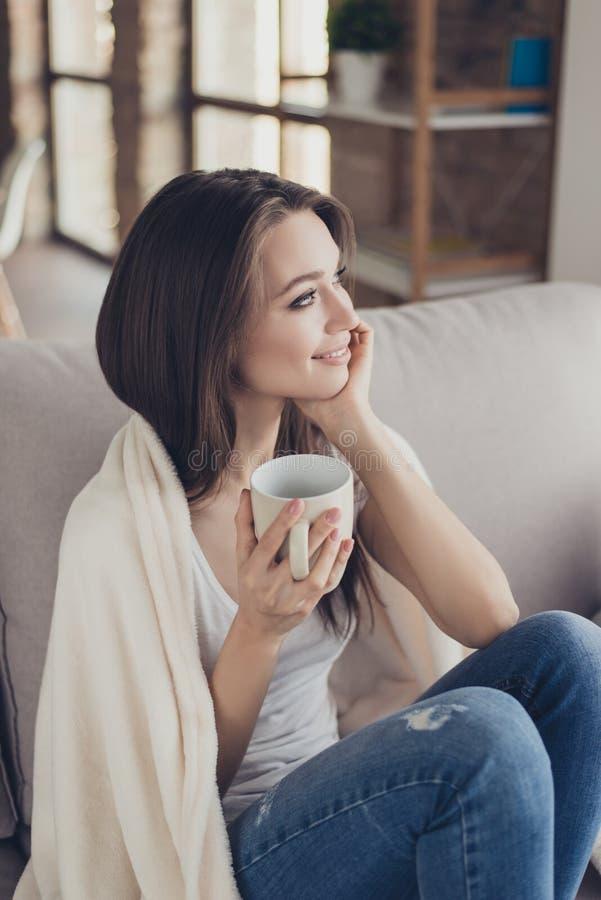 Porträt der recht jungen Frau, die auf Couch im Plaid und im dri sitzt lizenzfreies stockbild