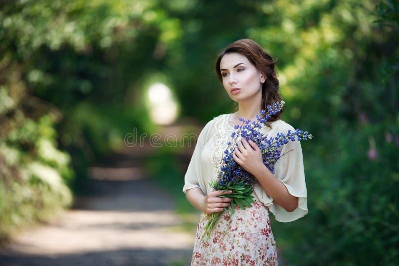 Porträt der recht jungen Frau, die in einen feenhaften Wald mit Blumenstrauß von Blumen geht lizenzfreies stockfoto
