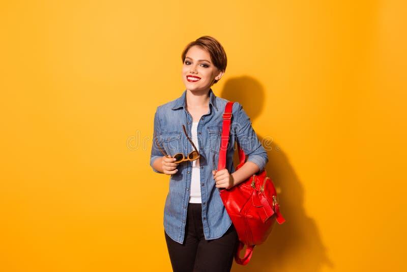 Porträt der recht jungen lächelnden Studentin kleidete in den Jeans an stockfoto