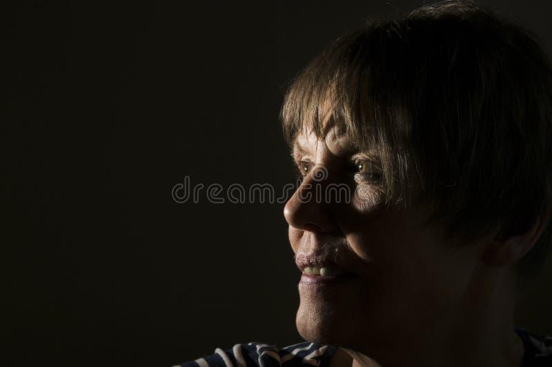 Porträt der reifen Frau auf Schwarzem stockbilder